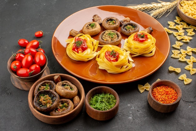 Front view cooked mushrooms with dough pasta on a dark table meal dish food dinner color