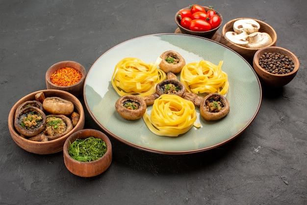 暗いテーブルに生地パスタを添えた正面図の調理済みキノコ、食用色素ディナーミール