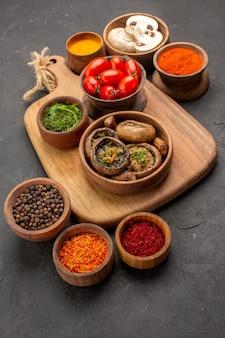 Вид спереди приготовленные грибы с приправами на темно-сером столе спелые дикие продукты