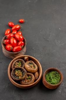 正面図暗いテーブルのキノコの野生のパスタにトマトと調理されたキノコ