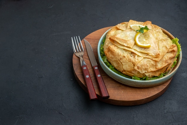 전면보기 어두운 표면에 채소와 레몬 슬라이스 접시 안에 피타 요리