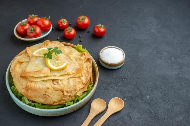 전면보기 어두운 표면에 녹색 레몬과 토마토와 함께 접시 안에 피타 요리