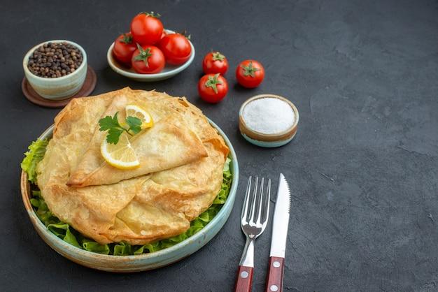 전면보기 어두운 표면에 레몬 슬라이스와 토마토와 함께 접시 안에 피타 요리