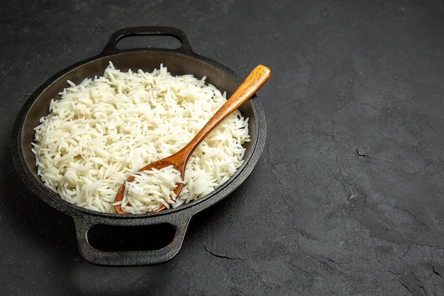 Vista frontale riso cotto all'interno della padella sulla superficie scura pasto cibo riso cena orientale
