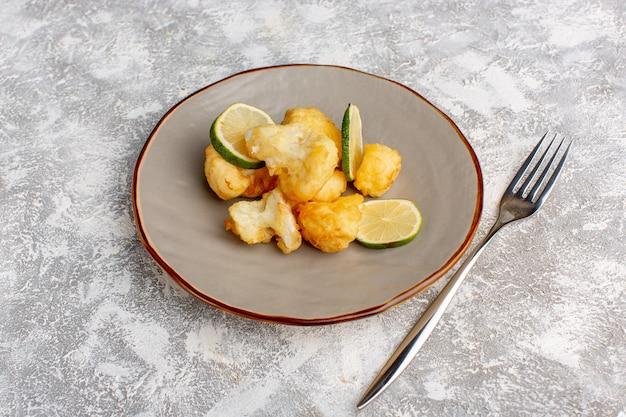 Vista frontale del cavolfiore affettato cotto all'interno del piatto con il limone sulla scrivania bianca