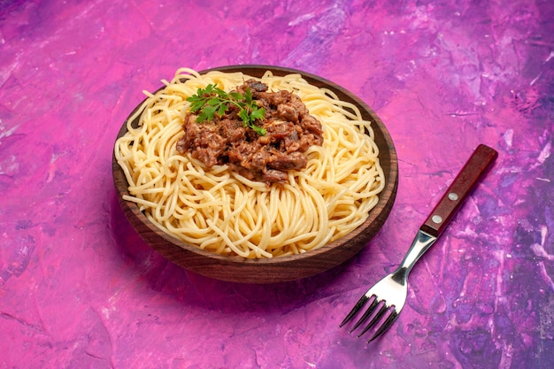 ピンクのテーブルカラーの皿生地パスタにひき肉を添えた正面図調理スパゲッティ