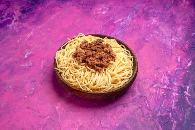 ピンクのテーブル皿パスタ色生地にひき肉と正面図調理スパゲッティ