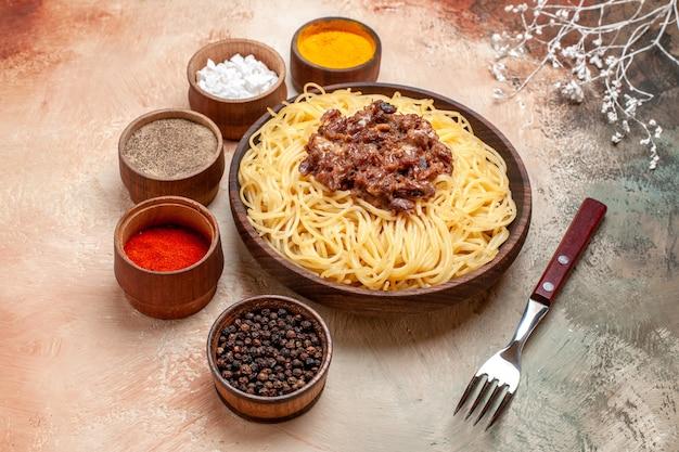 ライトテーブルのパスタ料理の食事の肉にひき肉を添えた正面図の調理済みスパゲッティ