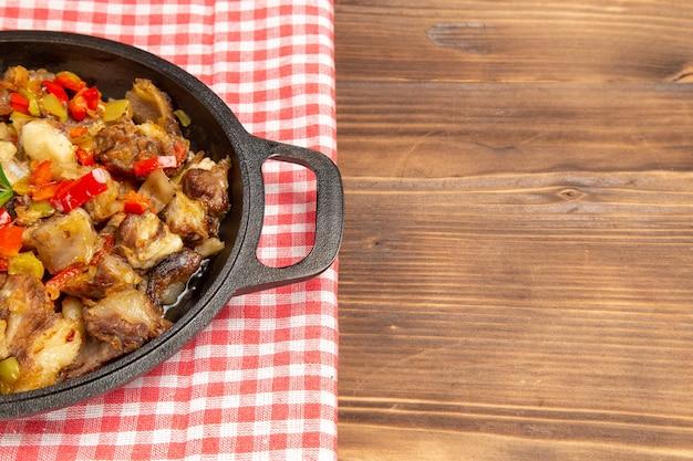 Farina di verdure cotte vista frontale comprese verdure e carne all'interno sullo scrittorio di legno marrone