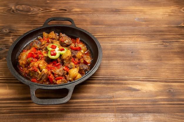 茶色の机の上の鍋の中の正面図調理野菜の食事