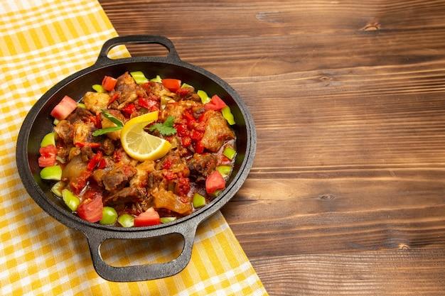 Приготовленная овощная еда с мясом и нарезанным перцем на коричневом столе, вид спереди