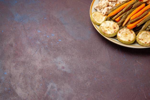 濃い紫色の机の上に卵の食事と一緒に調理された野菜の正面図