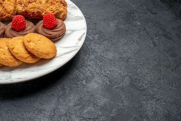 灰色の机の上のプレート内の正面のクッキーとケーキ