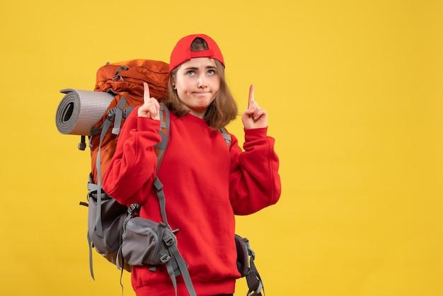 배낭 가리키는 손가락을 가진 전면보기 멋진 여성 여행자