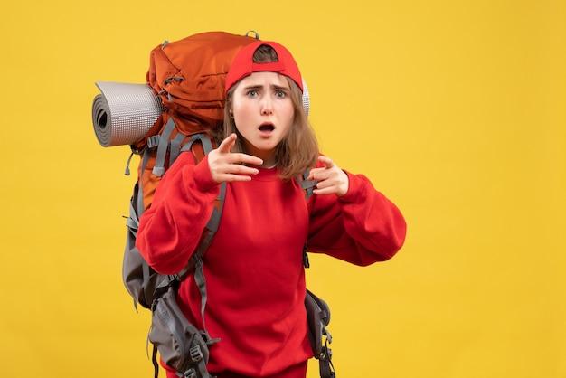 Вид спереди крутая путешественница с рюкзаком, указывающая пальцами на камеру