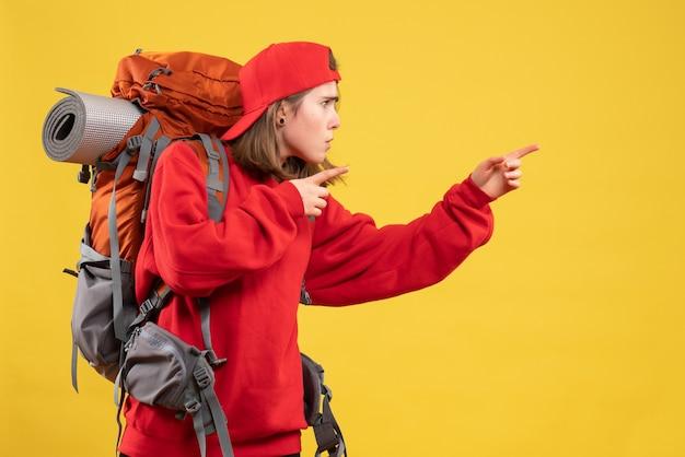 Viaggiatore femminile freddo vista frontale con zaino che punta con le dita a destra