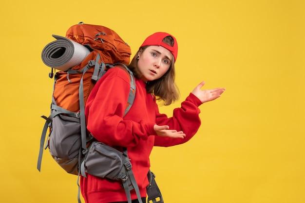 Viaggiatore femminile freddo di vista frontale con lo zaino che mostra qualcosa