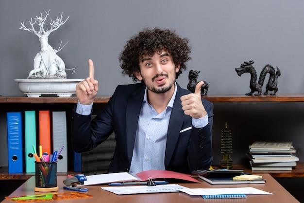 Вид спереди прохладный офисный работник, показывая пальцы вверх, сидя за столом в офисе