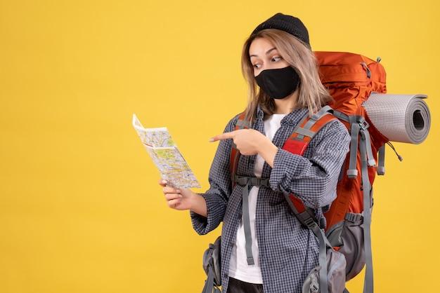 Vista frontale della ragazza cool viaggiatore con maschera nera e zaino guardando la mappa