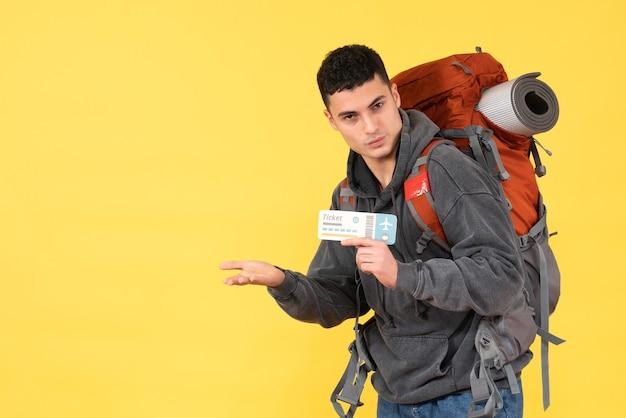 Uomo fresco del viaggiatore di vista frontale con lo zaino rosso che tiene il biglietto di viaggio su colore giallo