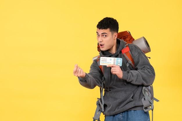 Vista frontale cool uomo viaggiatore con zaino rosso che tiene il biglietto di viaggio