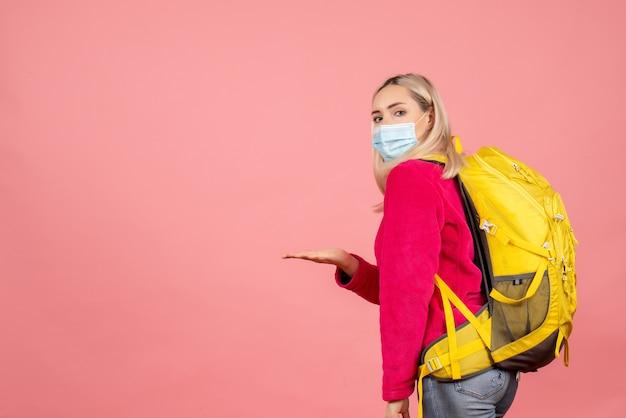 마스크를 쓰고 노란색 배낭 전면보기 멋진 여행자 여자