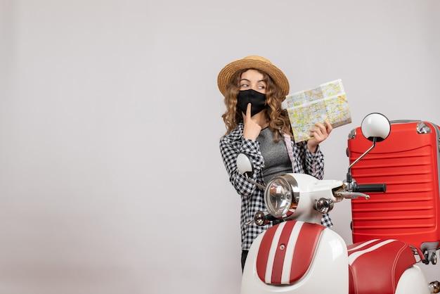 Vista frontale della ragazza giovane fresca con maschera nera che tiene mappa in piedi vicino al ciclomotore rosso