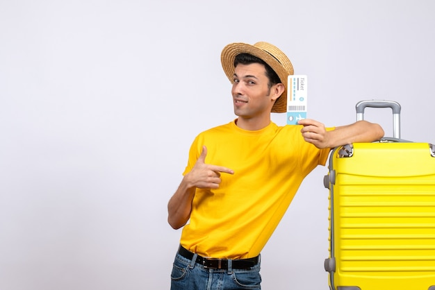 Vista frontale cool giovane turista in piedi vicino alla valigia gialla che punta al biglietto