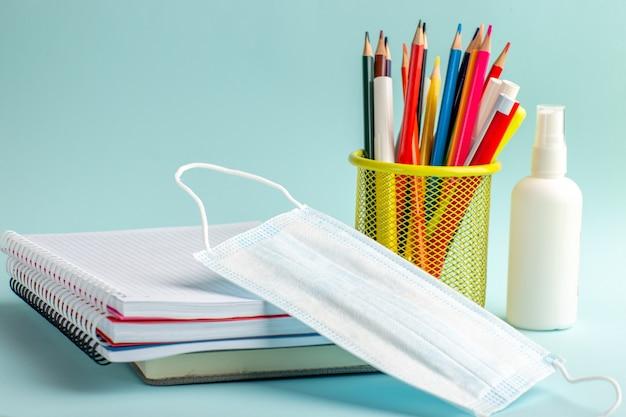 Quaderni di vista frontale e penne matite colorate maschera e spray sulla superficie blu