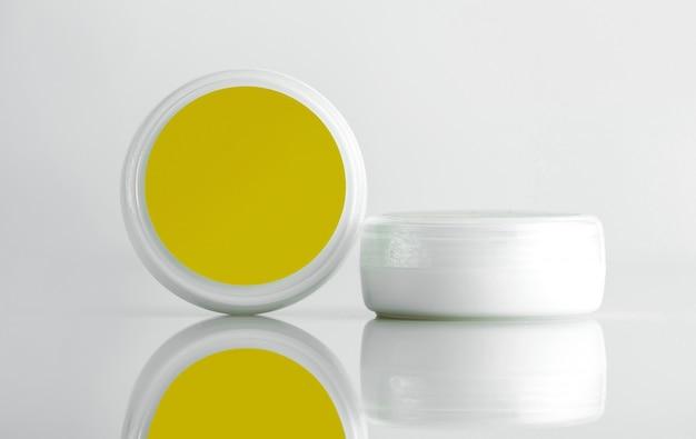 Вид спереди косметическая банка для крема белая банка с желтой крышкой