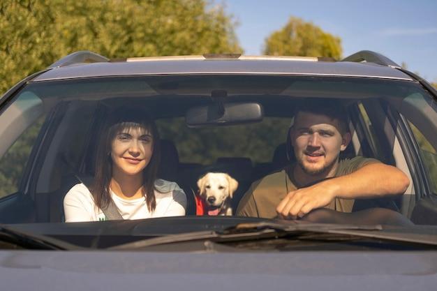 車の正面のカップルと犬