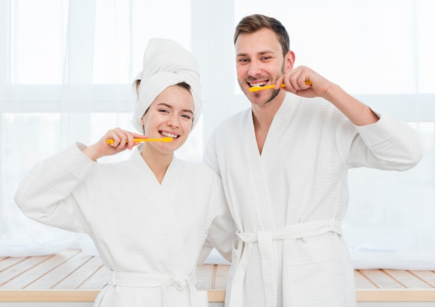 Front view of couple in bathrobes brushing their teeth