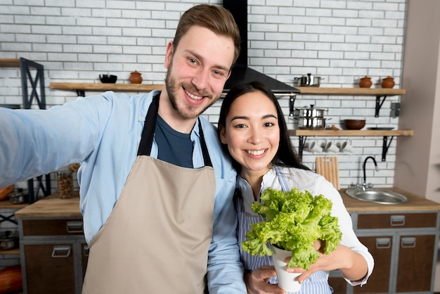 Front view of couple capturing selfie with woman holding fresh green lettuce in kitchen