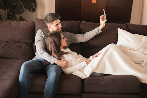 Front view couple on couch taking selfie