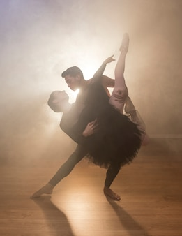 Front view couple dancing in smoke