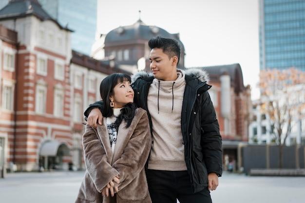 Vista frontale della coppia abbracciata all'aperto in città