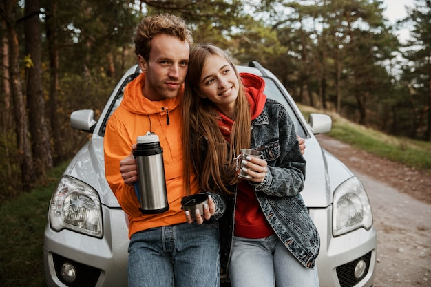 Front view of couple enjoying hot beverage while sitting on the hood of the car outdoors