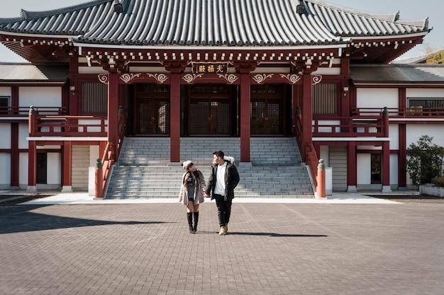 Vista frontale delle coppie davanti all'edificio giapponese