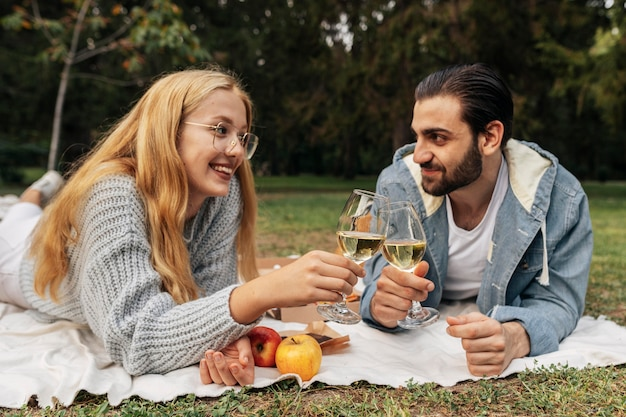 Front view couple having a glass of wine outside