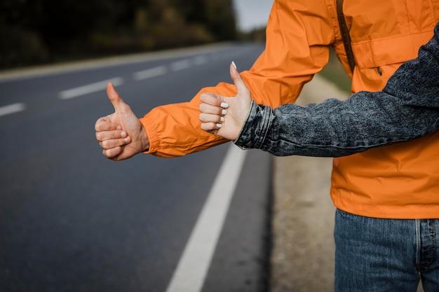 Vista frontale della coppia autostop durante un viaggio su strada