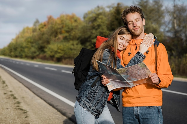 Front view of couple holding map and sitting along the road