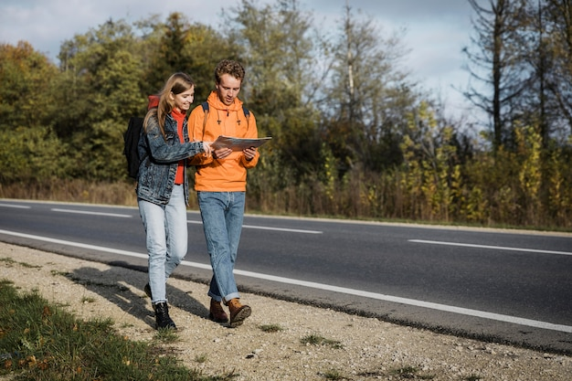 Front view of couple holding map and walking along the road