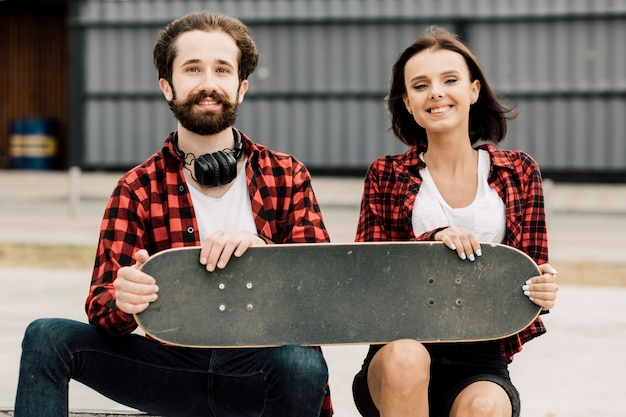 Front view of couple holding skateboard