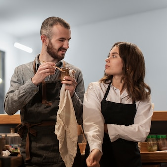 Front view of couple looking at each other wearing aprons