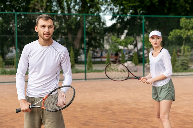 Front view couple playing tennis