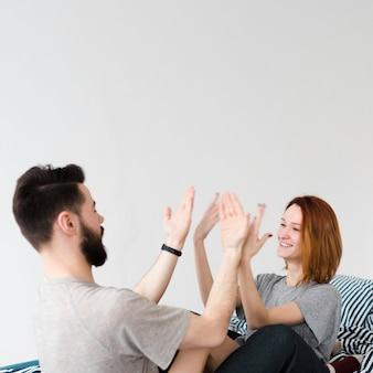 正面のカップルが自分の手で遊んで