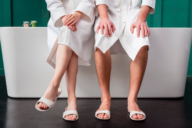 Front view of couple posing in bathrobes and slippers