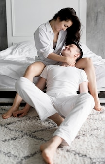Front view of couple posing next to bed at home