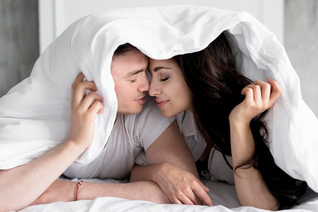 Front view of couple posing in bed with blanket over heads