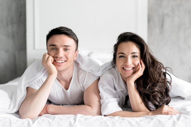Front view of couple posing in bed